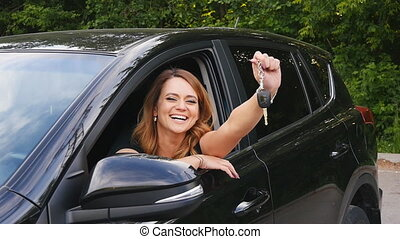 Woman driver holding car keys driving her new car