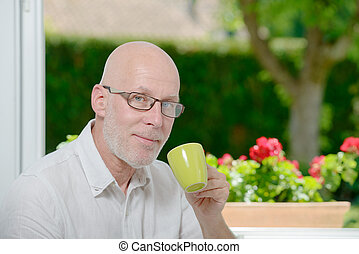 Mature man at home with cup of coffee