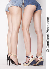legs of young women, pair butts in jeans shorts - legs of...