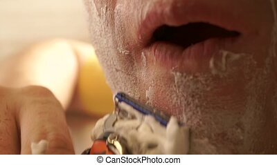 Young handsome man shaving his face, close up shot