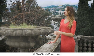 Portrait of fashionable girl at red dress She comes to the...