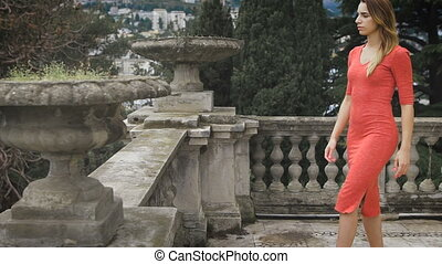 Portrait of fashionable girl at red dress. She comes to the...