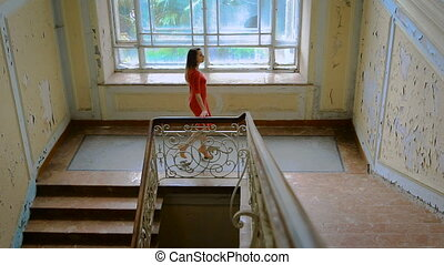 Beautiful girl in a red dress goes up the stairs. Abandoned...