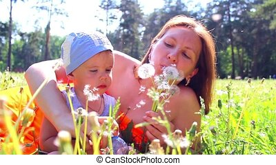 Mom with a child playing with dandelions