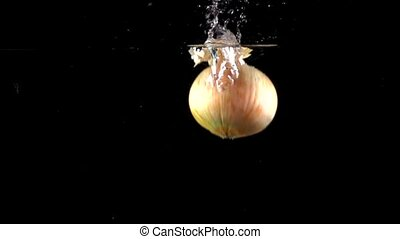 Super slow motion: whole onion falling into water, black...