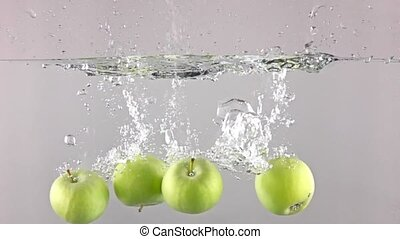Four green apples fall down in water against gray background, super slow motion
