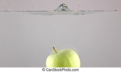 Green apple falls down in water, close up, gray background,...