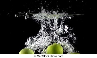 Super slow motion video: falling four green apples and splashes of water