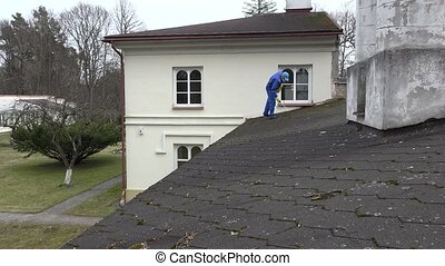 House cleaning service man spray moss with chemicals on roof...