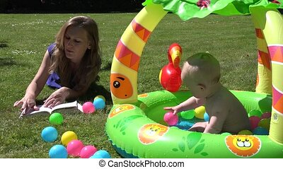 Woman read book on grass and play with baby son boy in kiddie pool. 4K