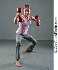 Teenage sportive girl is doing exercises with dumbbells to develop muscles on grey background. Sport healthy lifestyle concept. Sporty childhood. Teenager exercising with weights.