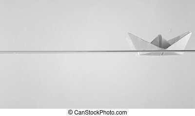 Paper boat blown away by wave, super slow motion. Insurance...