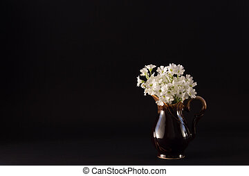 bouquet of small white flowers in a ceramic jug on a black background