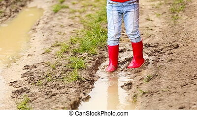 girl in rubber boots walks through the puddles