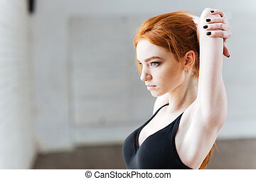 Close-up portrait of young woman streching at the gym -...