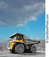 Mining Dump Truck - Heavy mining truck driving through the...