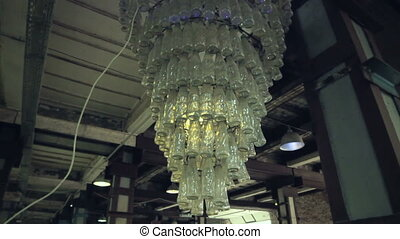 Retro chandelier made of bottles. Light of different colors.