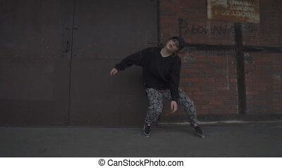 Female dancing on the brick wall