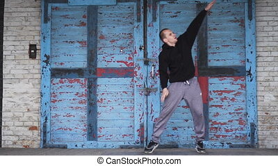 Male dancing over blue door - Active young male dancing...