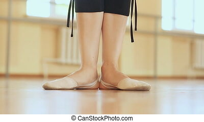 Young ballerina dancing, closeup on legs and shoes.
