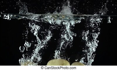 Three potatoes falling in water against black background. Super slow motion shot