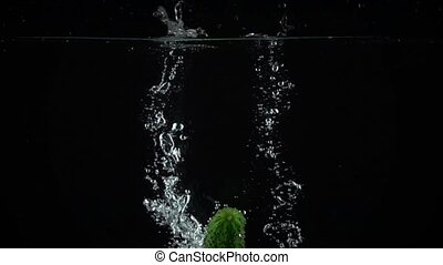 Two green cucumbers falling down in water, super slow motion...