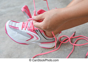 Woman is put on the pink sport shoes