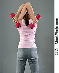 Teenage sportive girl is doing exercises to develop with dumbbells muscles on grey background. Sport healthy lifestyle concept. Sporty childhood. Teenager exercising with weights.