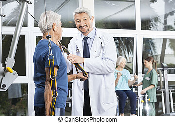 Happy Mature Doctor Assisting Senior Man With Resistance...