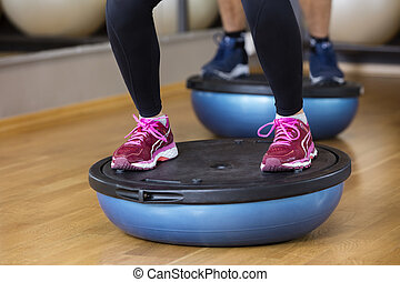 Low Section Of Woman Standing On Bosu Ball - Low section of...
