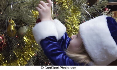 Maiden near Christmas tree - Snow Maiden girl hangs on a...