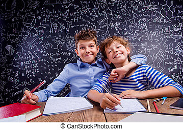 School boy and girl at the desk, big blackboard - Young...