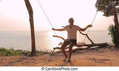 A man swinging on a swing - Man in sunglasses sitting on the...