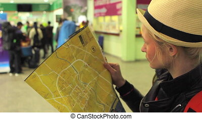 Girl looking at the map attentively - Girl in light hat...