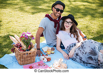 Smiling young couple having picnic on the lawn in park -...