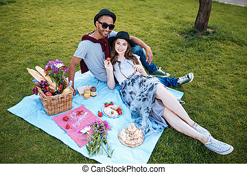 Beautiful smiling couple lying and relaxing outdoors - Top...