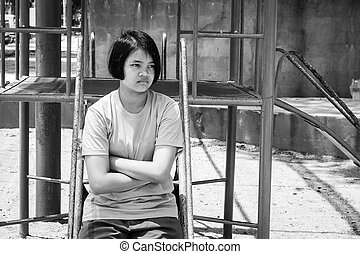 asian girl sitting alone at playground