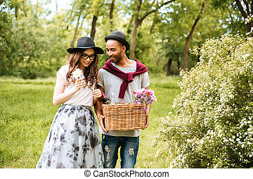 Happy young couple going to have picninc in park - Happy...