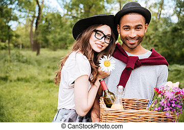 Happy young couple with basket of drinks, food and flowers -...