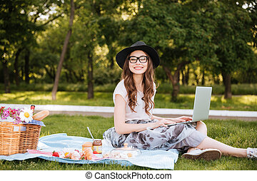Smiling pretty young woman using laptop on picnic in park -...