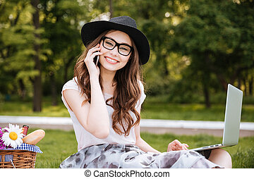 Cheerful woman alking on cell phone and using laptop outdoors