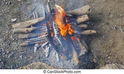 wood burning fire - firewood, stacked crosswise fire burning...
