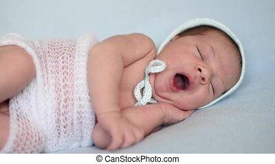 cute newborn baby yawns - newborn baby yawns lying on a blue...