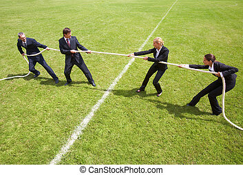 Competition - Businessmen and businesswomen playing tug of...
