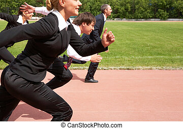Race - Image of active employees running down sport track