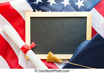 board, bachelor hat and diploma on american flag -...