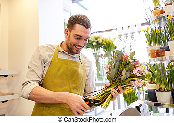 smiling florist man making bunch at flower shop - people,...