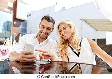 happy couple with smatphone at restaurant terrace - love,...