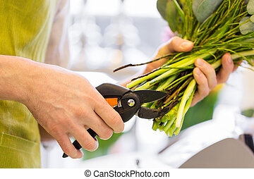 close up of florist man with flowers and pruner - people,...