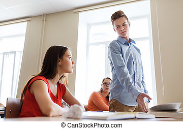 students gossiping behind classmate back at school -...
